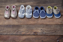 Four pairs of baby booties. On a wooden background stock photos