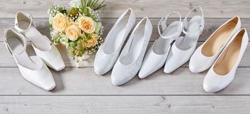 Four pairs of different white wedding shoes. Four pairs of different white high heeled classic wedding shoes in assorted styles arranged in a row with a bridal royalty free stock images