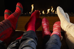 Four pairs feet in socks warming by fire Stock Photo