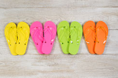 Four pairs of New Sandals on faded white wood Royalty Free Stock Photo