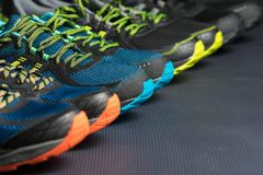 Four pairs of running shoes / fitness trainers. Four pairs of running shoes / exercise trainers lined up in a row on a gym floor with potential text / writing stock images