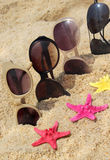 Four pairs of sunglasses on the beach Royalty Free Stock Photos