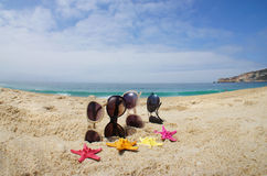 Four pairs of sunglasses on the beach Stock Images