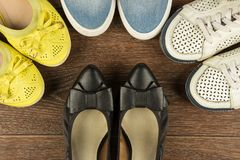Four pairs of women`s shoes of white, yellow, blue and black on. Four pairs of women`s shoes of white, yellow, blue and black are on the brown floor flat lay Stock Photos