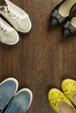 Four pairs of women`s shoes of white, yellow, blue and black on. Four pairs of women`s shoes of white, yellow, blue and black are on the brown floor flat lay Stock Photo