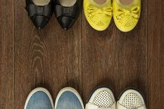Four pairs of women`s shoes of white, yellow, blue and black on. Four pairs of women`s shoes of white, yellow, blue and black are on the brown floor flat lay Royalty Free Stock Photo
