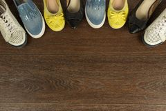 Four pairs of women`s shoes of white, yellow, blue and black on. Four pairs of women`s shoes of white, yellow, blue and black are on the brown floor flat lay Stock Photography