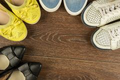 Four pairs of women`s shoes of white, yellow, blue and black on. Four pairs of women`s shoes of white, yellow, blue and black are on the brown floor flat lay Stock Images