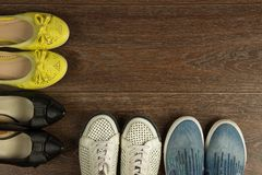Four pairs of women`s shoes of white, yellow, blue and black on. Four pairs of women`s shoes of white, yellow, blue and black are on the brown floor flat lay Royalty Free Stock Image