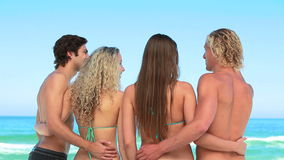 Four pals embrace each other at the beach Royalty Free Stock Photography