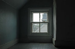 Four-Pane Window in an Attic. Four-Pane window with antique glass in a dimly-lit attic. Light blue wallpaper and wood floors. Has a moody sad atmosphere royalty free stock image