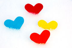 Four paper colored heart shapes in snow Royalty Free Stock Images