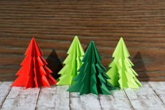 Four paper origami Christmas trees on a wooden background. Four green and red paper origami Christmas trees on a wooden background Royalty Free Stock Images