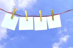 Four Papers pinned. In a line with the sky in the background Stock Images