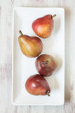 Four Pears On White Dish Stock Image