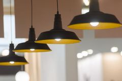 Four pendant lamps blurred background. Four hanging lamps in a line blurred background Stock Photos