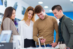 Four people are choosing smart phones. In the store Stock Photography