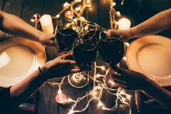 Four people clinking glasses with wine. Cropped shot of four people clinking glasses with red wine over served table with fairylights decorations Stock Photo