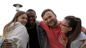 Four people of different nationalities stand embracing. Concept of relationships and unity between different human races