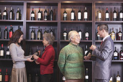 Four people examining and discussing wine at a wine store Stock Photography