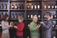 Four People Examining Wine Bottles at a Wine Store Royalty Free Stock Photos