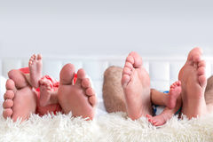 Four people family feet. Father, mother, baby boy and baby girl Stock Photo