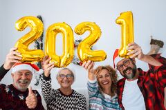 Four people having fun and smiling together at home holding up the four balloons numbers of the 2021 - family laughing and