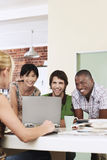 Four people having meeting around laptop laughing. Stock Photos
