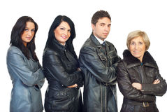 Four people in leather jackets. Four people  wearing different  leather jackets colors and models and standing  in a line in semi profile  with hands crossed Royalty Free Stock Photography