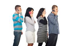 Four people in a line talking by cellphones stock image