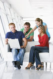 Four people in lobby pointing at laptop smiling Stock Images
