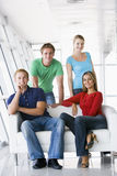 Four people in lobby smiling Stock Photo