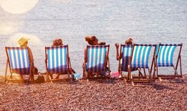 Four People On Lounge Chairs Near The Beach royalty free stock photography