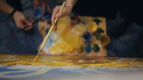 Four people painting together with paintbrushes on the white canvas stock video