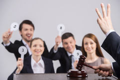 Four people raising cards with number. Royalty Free Stock Photos