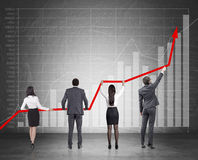 Four people and red graph. Rear view of four colleagues holding a growing graph against blackboard with stats. Concept of making successful business. Mock up Royalty Free Stock Image
