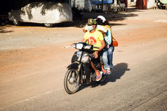 Four people riding one motorbike in Cambodia. The only evidence being the number of legs Royalty Free Stock Photos