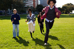 Four People Running Through an Urban Park Royalty Free Stock Photography