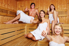 Four people in sauna holding thumbs Stock Images