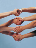 Four people shaking hands Stock Images