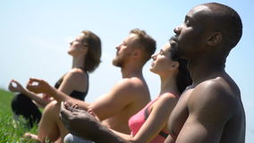 Four people sit on the grass and meditate, close up stock video footage