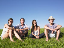 Four People Sitting on the Grass Stock Images
