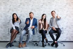 Four people are sitting and showing a thumbs-up gesture on her outstretched hand and smiling. stock photography