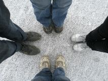 Four people stand in different shoes on the white surface of the earth royalty free stock photos