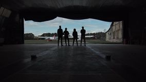 Four people standing in an aircraft hangar. Silhouetted against the sky watching two small aircraft outside in a low angle view stock footage