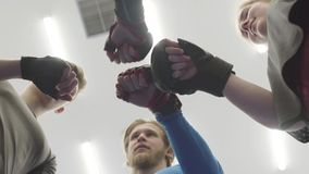 Four people standing in the circle above the camera in the gym. A company of male and female athletes put their fists in. Four people standing in the circle stock video