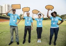 Four People Standing on Field Holding Conversation Bubbles Stock Images