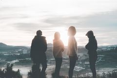 Four People Standing on Top of Hill during Sunset royalty free stock photos