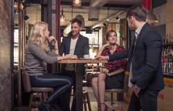 Four people talking, small group of people talking, coffee shop. Four people talking, standing sitting, small group of people talking, coffee shop indoors, men Stock Photos