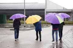Four people under colorful umbrella's Stock Images